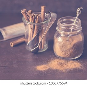 Ground cinnamon and cinnamon sticks with tongs and grater on brown background. Toned photo.