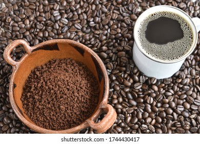 ground coffee in artisan dish and cup of coffee on a background of coffee beans
