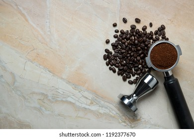 Ground coffee, coffee beans with filter holder and tamper on textured background with selective focus, Flat lay, Copy space