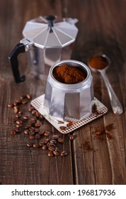 Ground coffee, coffee beans and Moka Pot coffee maker over rustic wooden background. Selective focus, shallow DoF