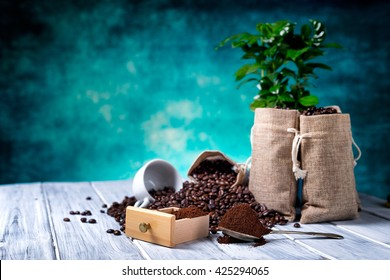 Ground coffee with coffe seeds and coffe plant with jute bags on the background.