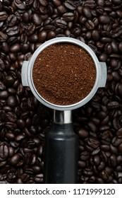 Ground coffee with filter holder on coffee beans textured background with selective focus, Flat lay