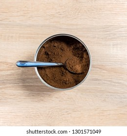 Ground coffee in a jar with a spoon inside, close up