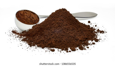 Ground coffee pile with metallic measuring scoop isolated on white background