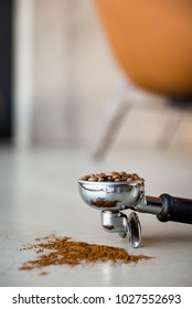 Ground coffee in porta filter with beans