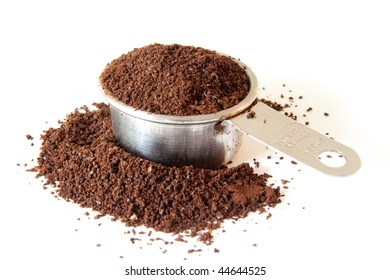 Ground coffee spilling out of a full coffee measure. Shot on white background. Focus is on the edge of the cup. Coffee in the foreground is out of focus.