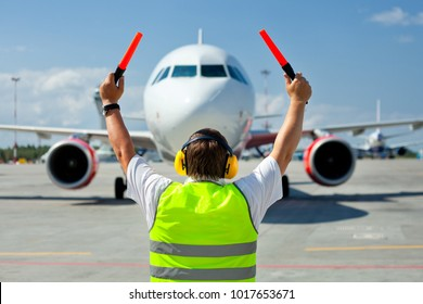 Ground Crew in the signal vest. Aviation Marshall / Supervisor meets passenger airplane at the airport. Aircraft is taxiing to the parking place.
