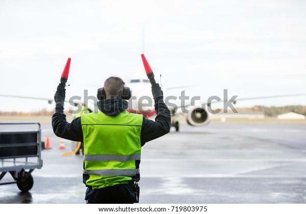 Ground Crew Signaling To Airplane