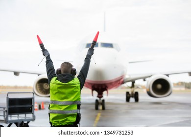Ground Crew Signaling To Airplane On Runway