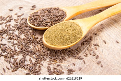 Ground cumin in a spoon and whole cumin on the wooden background.
