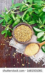 Ground fenugreek in a spoon and seeds in a bowl on burlap with green leaves on wooden board background from above