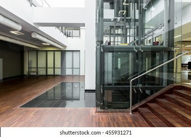 Ground floor of a modern building with glass elevator core in the middle