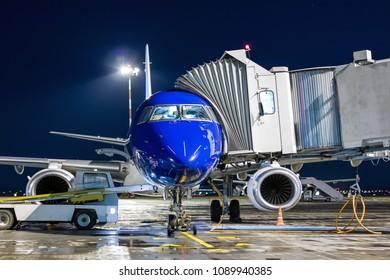Ground handling of airplane near a passenger ramp at night