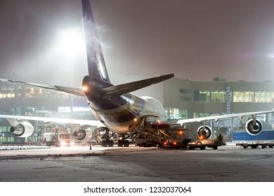 Ground handling passenger airplane at night winter airport