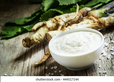 Ground horseradish, hot sauce to the food in a white bowl, roots and leaves of fresh horseradish, vintage wooden background, selective focus