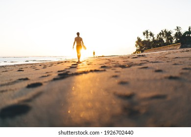 Ground level back view of unrecognizable male surfer with naked torso walking on sandy seashore with footprints holding surfboard in evening in colorful sunshine