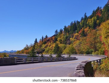 Ground level, or road level, view of the S curve on the Blue Ridge Parkway's Linn Cove Viaduct in North Carolina where it wraps around Grandfather Mountain. More mountains & blue sky in background.