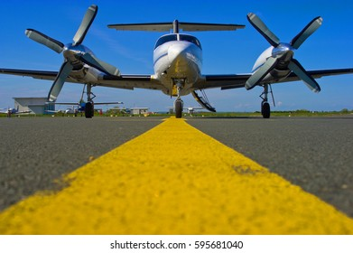 Ground level shot of a business turboprop awaiting passengers for the next flight under a blue sky.