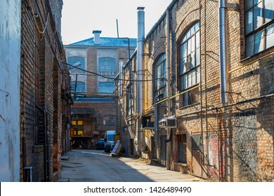 Ground level view from brick paving stones of old warehouse exterior with large windows and dock doors.