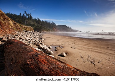 Ground level view  of Indian Beach at Ecola State Park in Oregon with a large log in the foreground.