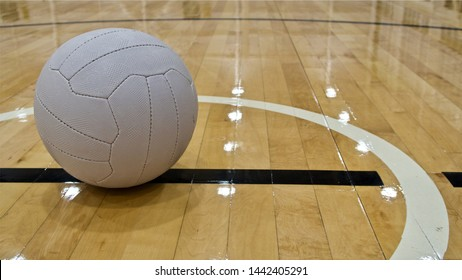 A ground level view of a Netball Ball positioned left of shot, placed within the centre circle on a wooden floorboard Netball Court.