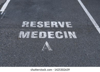 Ground marking in french (reserve medecin) on asphalt in a car park: reserved for the doctor.