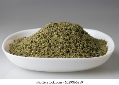 Ground medical cannabis in white plate on white background ready to be processed for production of cannabis oil, close-up, selective focus