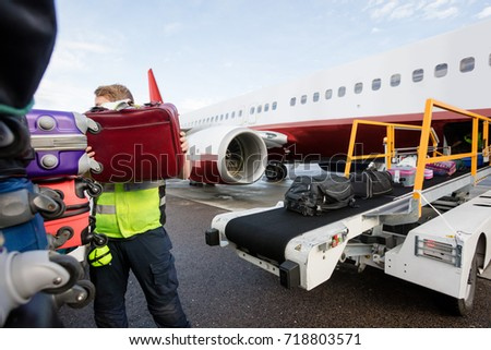 Ground Member Stacking Bags On Trailer At Runway