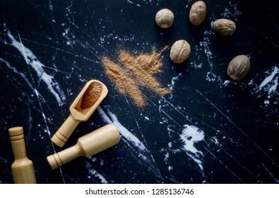 Ground nutmeg on dark background.  Powder nutmeg on a wooden bucket. Nutmeg seeds and nutmeg powder on table