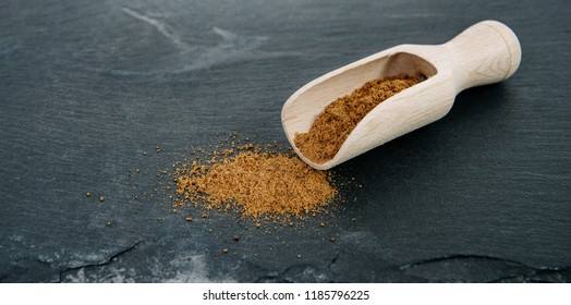Ground nutmeg on a dark, stone counter top. Powder nutmeg on a wooden bucket. The concept of using herbs and spices for dishes. Improving the taste. Adding clarity to dishes.