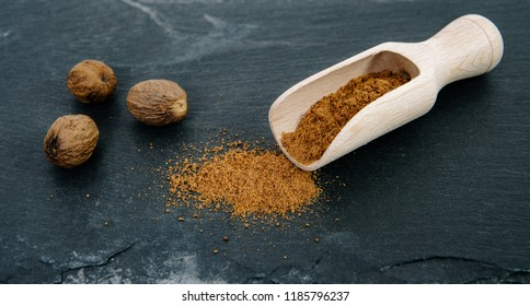 Ground nutmeg on a dark, stone top and whole nutmeg nut seeds. Powder nutmeg on a wooden bucket. The concept of using herbs and spices for dishes. Improving the taste.