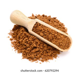 ground nutmeg powder n a wooden scoop for spices close up isolated on a white background
