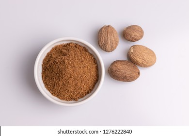 Ground nutmeg spice in white ceramic bowl isolated on white background, soft light, studio shot, copy space, top view.