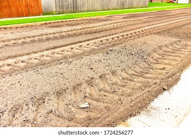 Ground up pavement after road pulverize came through grinding up the worn out tarmac in preparation for new road.  The street is turned into gravel with deep machine tire tracks.