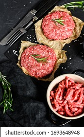 Ground raw meat patties. Meat patties ready to cook. Barbecue party. Farm organic meat. Black background. Top view