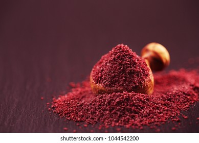 Ground Red Sumac Berries spice on black plate
