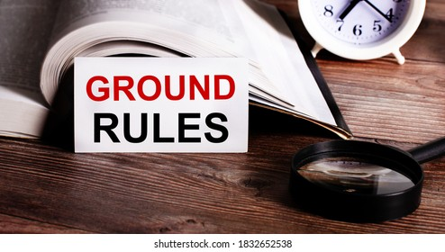 GROUND RULES written on a white card near an open book, alarm clock and magnifying glass