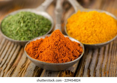 Ground spices on spoons on a wooden background