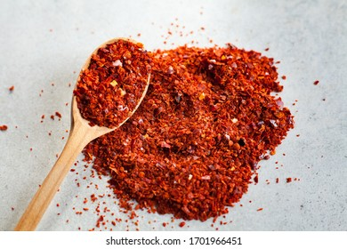 Ground spices of red pepper, paprika in a wooden spoon on a gray background