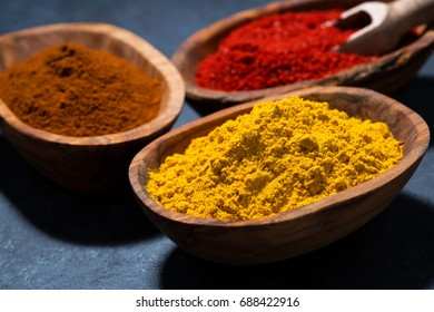 ground spicy paprika, turmeric and red pepper in a wooden bowl, closeup