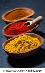 ground spicy paprika, turmeric and red pepper in a wooden bowl, vertical, closeup