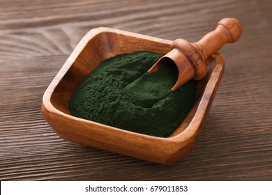 Ground Spirulina on wood background