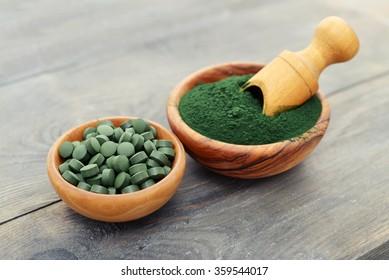 Ground spirulina and spirulina in pills over black wooden background