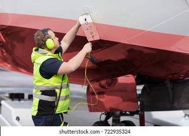 Ground Staff Member Adjusting Communication Cable On Outer Airpl