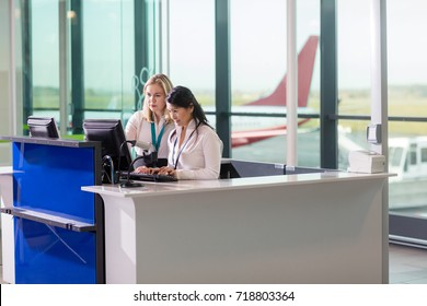 Ground Staff Using Computer At Counter In Airport