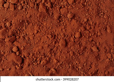 Ground Texture. Top View of a Red Ground Surface. Close Up Macro View of Dirt and Stones. Soil Background with Text Space.