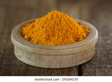 Ground turmeric in a bowl on wooden surface