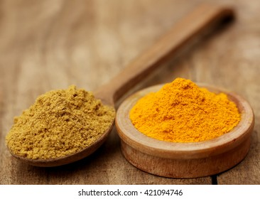 Ground turmeric and coriander on wooden surface