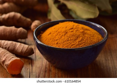 Ground turmeric powder in a bowl on wooden background. Healthy spice.