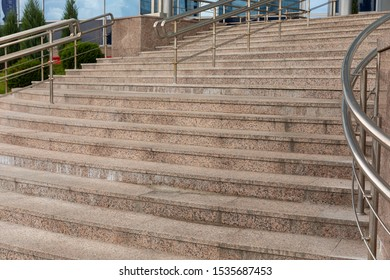 Ground view of concrete tiled ascending stairs with stainless banister